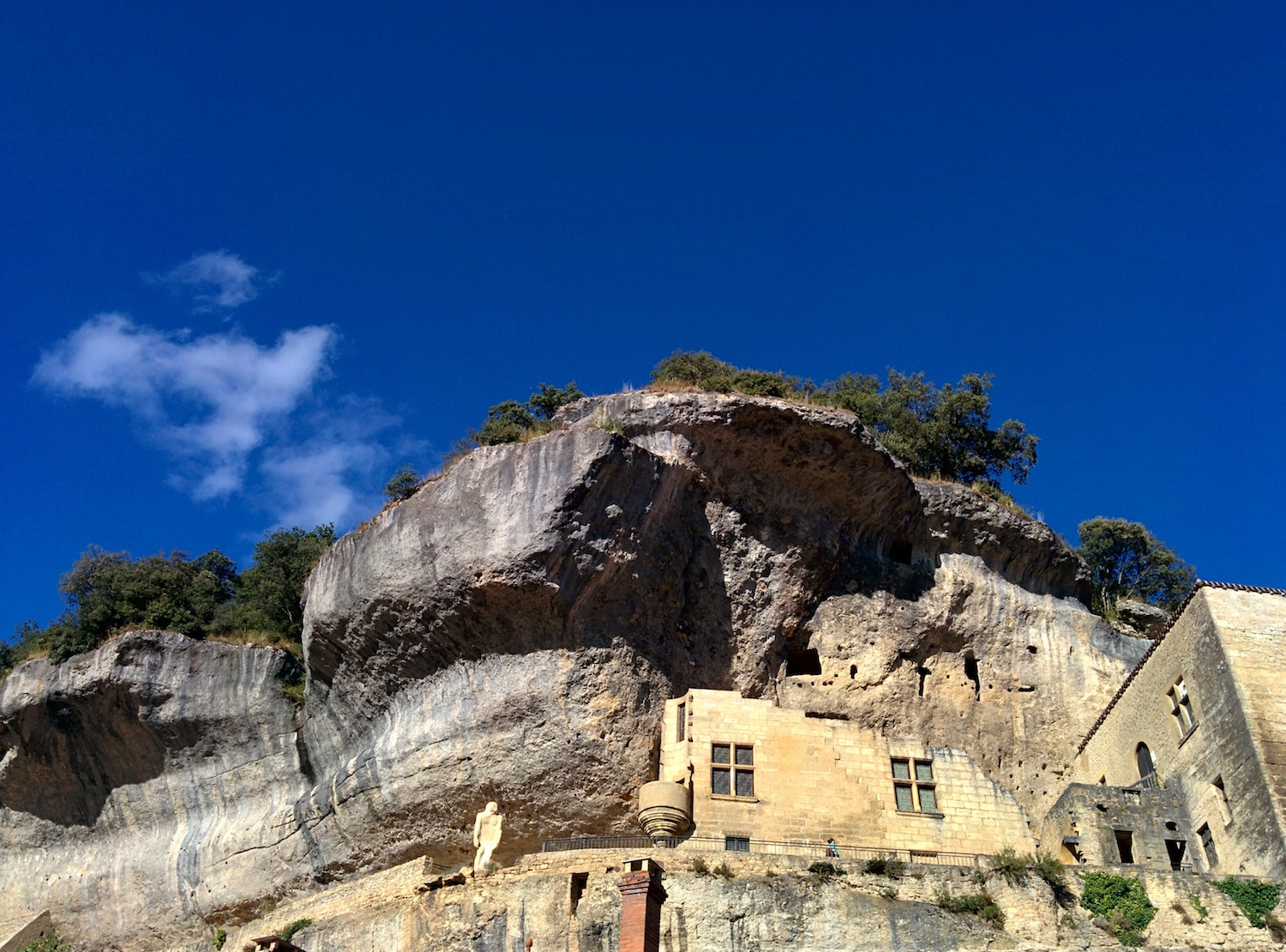 Buildings merge with the cliffs at Les Eyzies, Dordogne, France.