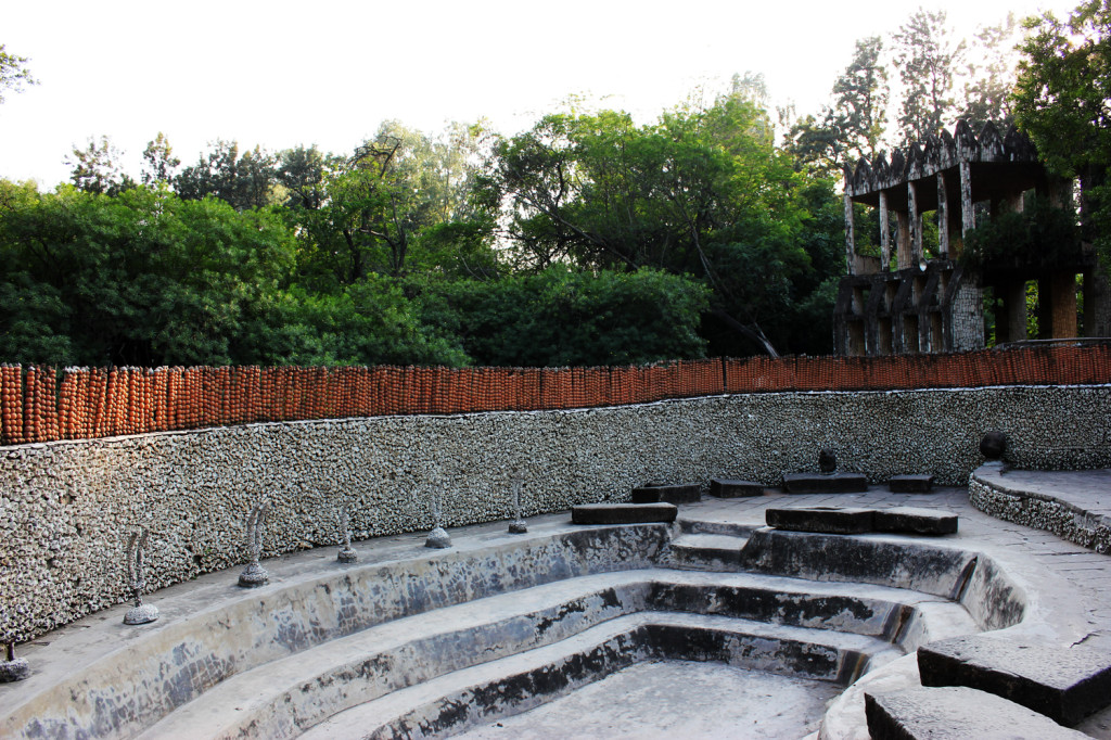 An amphitheatre enclosed by a wall constructed from terracotta pots and broken light sockets. Copyright Simon Bonneau.